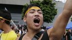 A pro-democracy activist shouts slogans on a street near the government headquarters where protesters have made camp