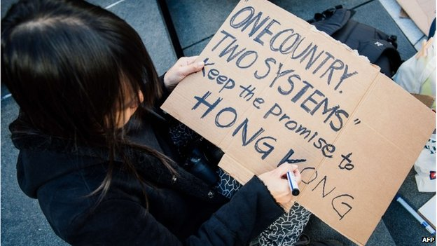 Woman writes a sign supporting Hong Kong at a protest in Stockholm, Sweden (1 Oct 2014)