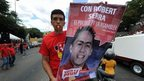 A man holds a poster of Robert Serra, candidate to the Congress, during a rally in Caracas on 22 September, 2010