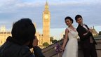 Couple pose for photographer (in shot) at the south end of Westminster Bridge