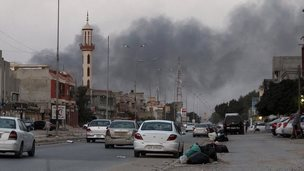 Smoke billows from buildings during clashes between Libyan security forces and armed Islamist groups in the eastern coastal city of Benghazi on 23 August 2014
