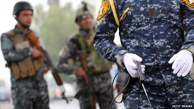 A member of the Iraqi security forces monitor a checkpoint using a fake explosive detecting device in the al-Jadriyah district of Baghdad on May 3, 2013.