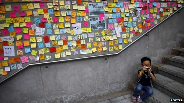 A boy takes pictures as he sits next to a wall covered with messages written by protesters outside the government headquarters in Hong Kong on 2 October 2014