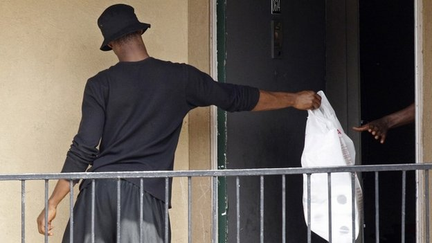 A man passes a bag, delivered by the Red Cross and the North Texas Food Bank, in to the apartment unit at The Ivy Apartments complex where a man diagnosed with the Ebola virus was staying in Dallas, Texas 2 October2014