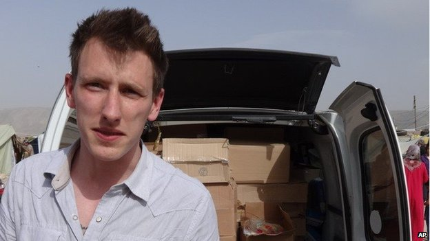 An undated photo provided by Kassig family shows Abdul-Rahman Kassig standing in front of a truck filled with supplies for Syrian refugees.