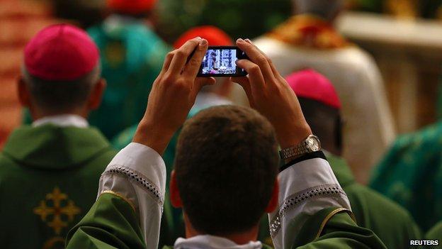 Un sacerdote toma una imagen como Papa Francisco celebra una misa con motivo de la apertura del Sínodo sobre la familia en la Plaza de San Pedro en el Vaticano, 05 de octubre 2014