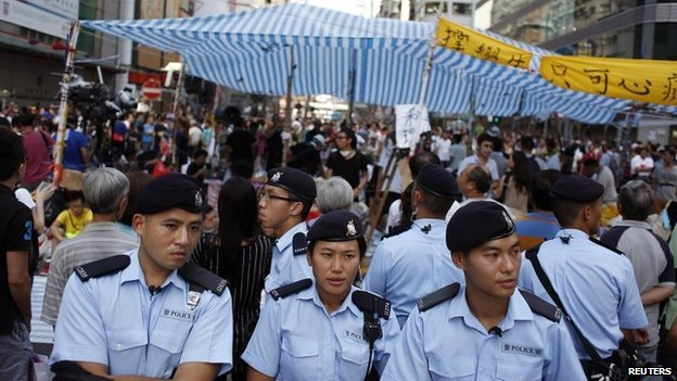 Policemen stand in front of protesters on a main road in Mong Kok district in Hong Kong - 5 October 2014