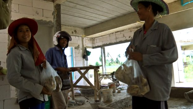Than Wai Aung sells mushrooms to some construction workers