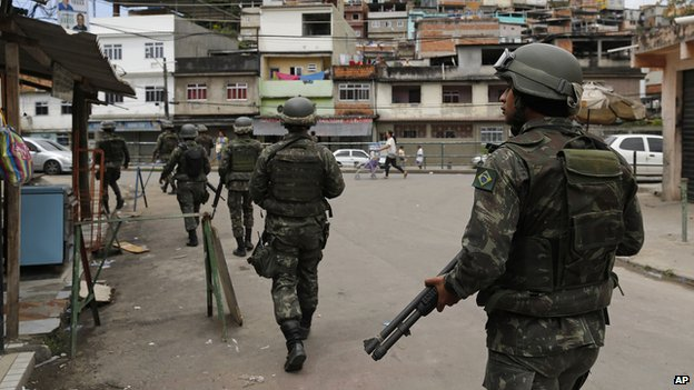 Soldiers patrol the alleys of the Mare Complex slum during general elections in Rio de Janeiro, Brazil, Sunday, Oct. 5, 2014