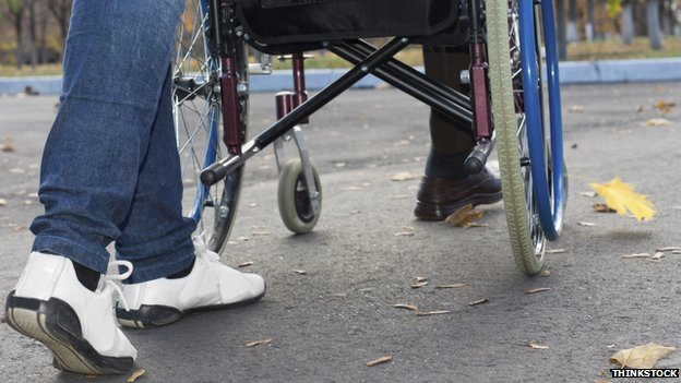 Shot of the legs of a person pushing a wheelchair user