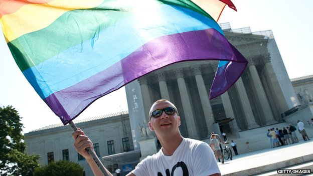A man waves a gay pride flag in front of the US Supreme Court building.