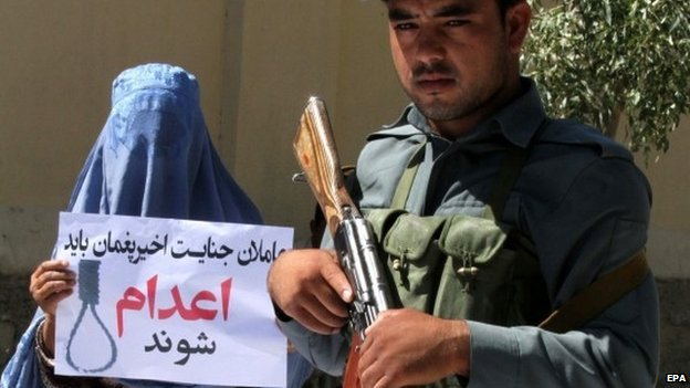 "An Afghan woman holds a placard reading in Darri ""Be executed"" during a protest against a high-profile gang rape case that shocked the capital Kabul, in Herat, Afghanistan, 08 September 2014"