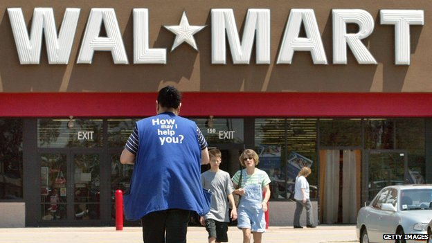 An employee stands outside of Walmart store.