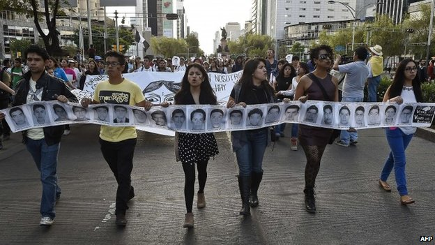 Demonstrators in Mexico holding a banner displaying the faces of missing persons.