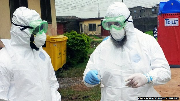 Doctors wearing personal protective equipment outside an Ebola treatment unit in Nigeria