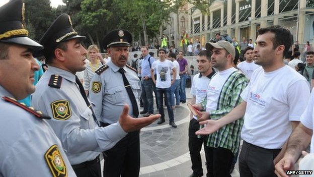 Rasul Jafarov (R) faces police in Azerbaijan on 23 May 2012
