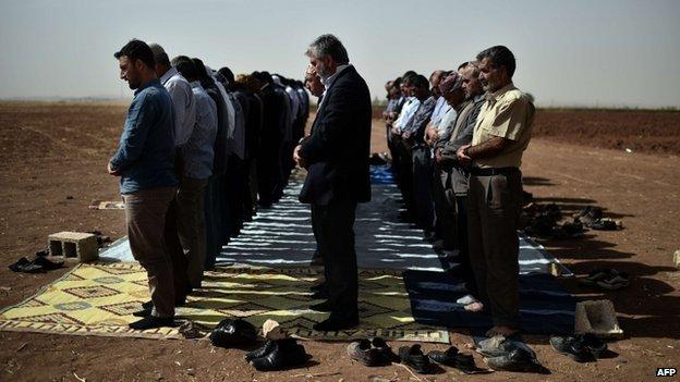 Syrian and Turkish Kurds pray during Friday prayers at the Turkish-Syrian border on 10 October 2014