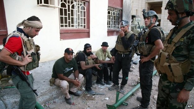 Iraqi security forces and gunmen rest on a sidewalk following clashes with jihadists in Ramadi, the capital of the western province of Anbar, 19 September 2014