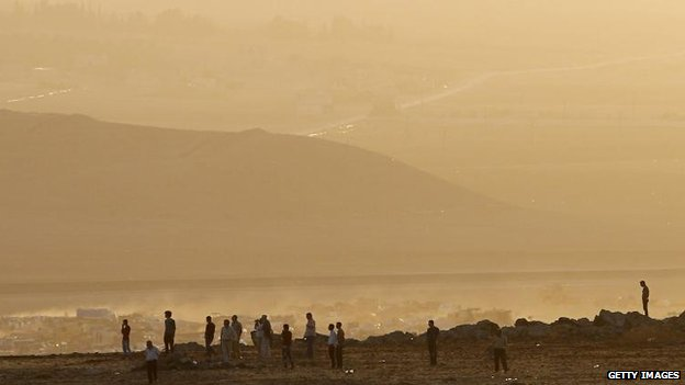 Syrian Kurds look over the border towards the fighting in Kobane, 10 Oct