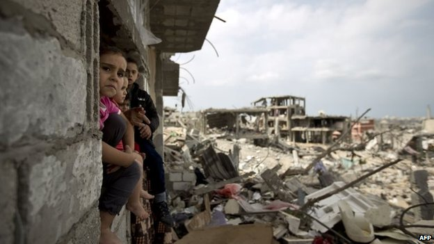 Palestinian children sit on the window of a partially destroyed building in al-Tufah, east of Gaza City, 11 October  2014