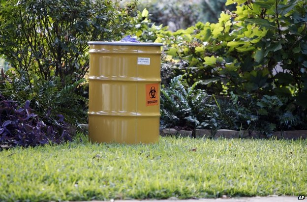 "A barrel labelled ""biohazard"" stands on a lawn outside the apartment complex of the infected health worker in Dallas, 12 October"
