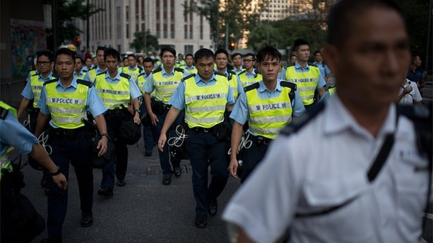 Police officers gather to remove pro-democracy protesters' barricades in the Admiralty district of Hong Kong