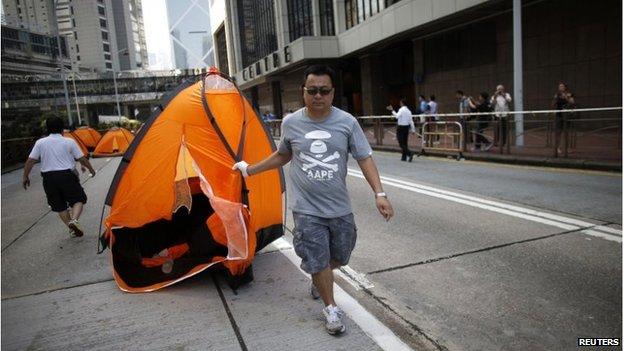 Man drags away a tent in Admiralty, Hong Kong (13 October 2014)