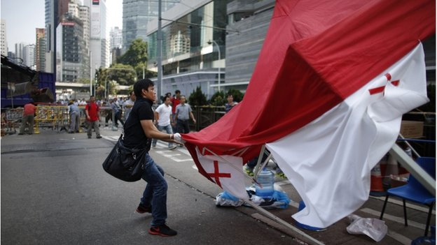 An Anti-Occupy Central protester drags away a tent at the main protest site in Admiralty in Hong Kong