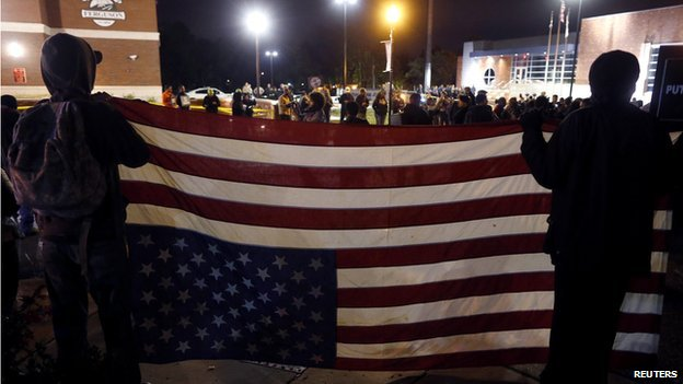 Protestors carry a US flag upside down at Ferguson protests