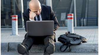 Man on curb with laptop
