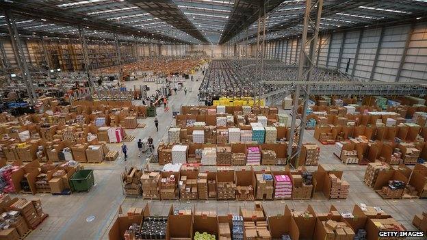 Boxes are piled inside of an Amazon warehouse.