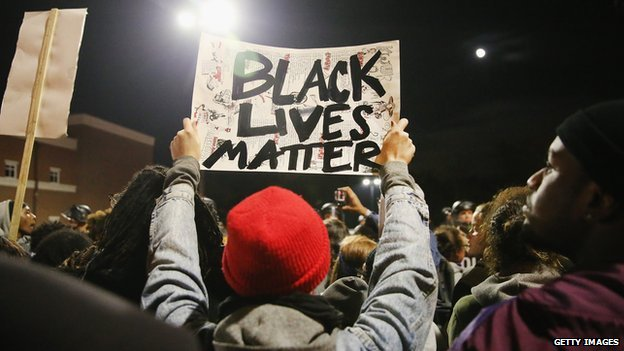 "A man holds up a sign reading ""black lives matter"" at a protest in Ferguson, Missouri."