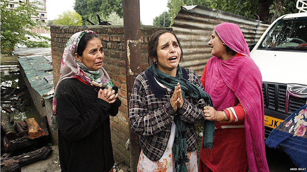 Kashmiri women wail as they stand near their submerged houses in Srinagar