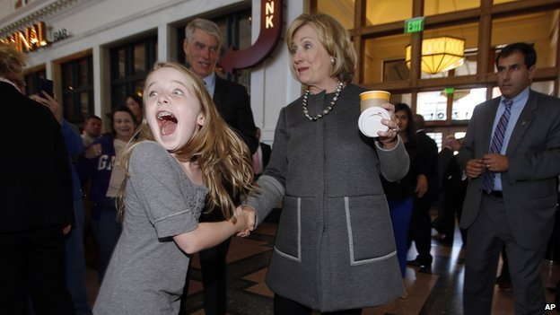 Macy Friday shakes the hand of former Secretary of State Hillary Clinton.