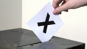 X on a piece of paper being put into a ballot box