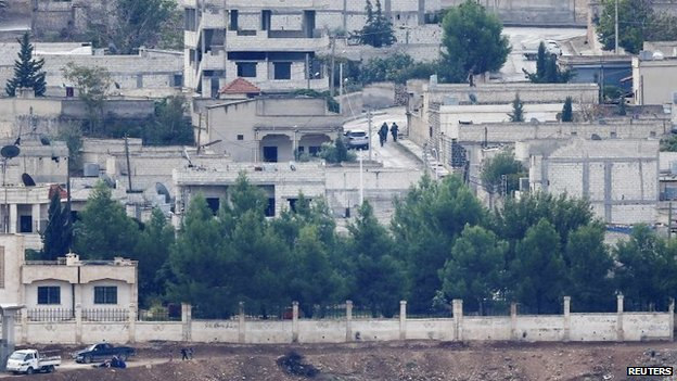 Unidentified armed men run through the Syrian town of Kobane (16 October 2014)