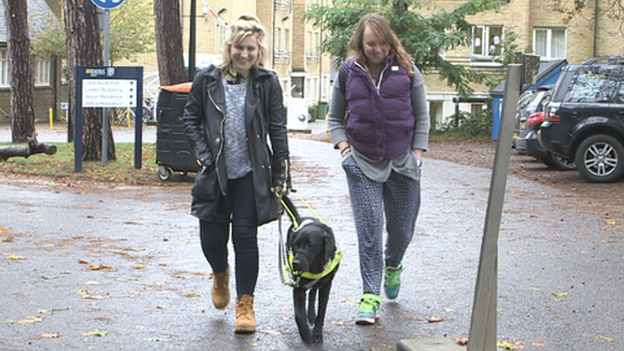 Molly with her guide dog and a friend walking outside her university