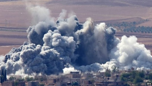 Smoke billows over a village near Kobane