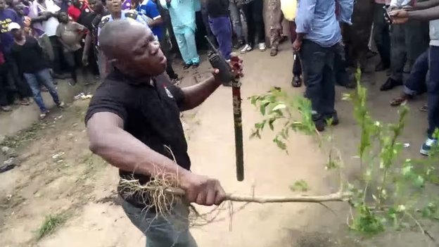 A man beating a crowd back with a branch