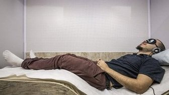 A man in Sao Paulo having a sleep at a branch of Cochilo