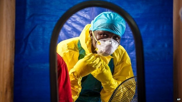 A medical worker dons protective gear before entering an Ebola treatment centre in Freetown, Sierra Leone - 16 October 2014