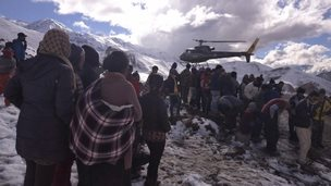 Handout photo of people gathering near a helicopter belonging to Nepal Army used to rescue avalanche victims at Thorang-La in Annapurna Region
