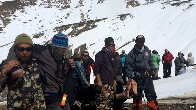 A survivor injured in a snowstorm is carried on a stretcher by Nepal Army personnel to an army helicopter in the Manang district along the Annapurna Circuit Trek, 17 October 2014