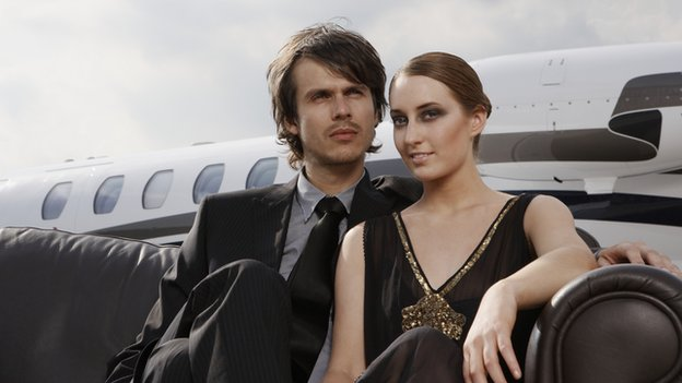 A young man and woman sit on a couch in front of a private jet.