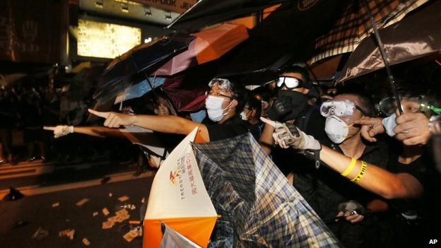 Pro-democracy protesters shout at advancing riot police on their encampment in the Mong Kok district of Hong Kong, early Sunday, Oct. 19