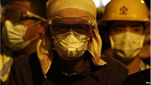 Pro-democracy protesters, their faces covered, gather during a demonstration in Mong Kok District of Hong Kong, 18 October