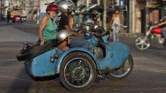 People ride in an Ural Soviet motorcycle in Havana, Cuba (9 October 2014)
