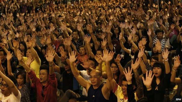 Pro-democracy advocates raise their hands in a symbolic show of peace and non-violence, during a rally of the ongoing Occupy Central movement at Admiralty district of Hong Kong, 19 October 2014