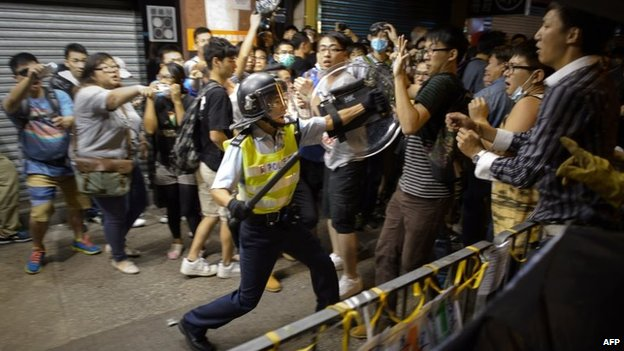 A policeman holding a baton advances towards pro-democracy protesters as they clash on a street in the Mong Kok district of Hong Kong early on 19 October 2014