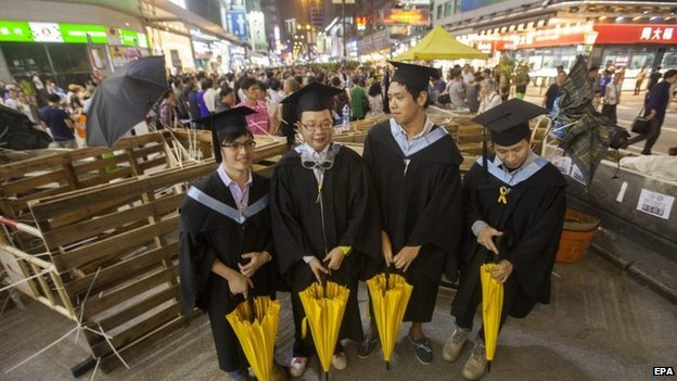 Graduates are seen in their caps, gowns and symbolic yellow democracy umbrellas by barricades in Mong Kok, 19 October 2014